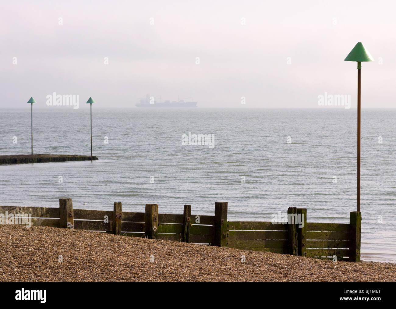 Épi en bois sur la plage à Leigh-on-Sea avec un navire à l'horizon. Leigh-on-Sea, Essex, Angleterre Photo Stock