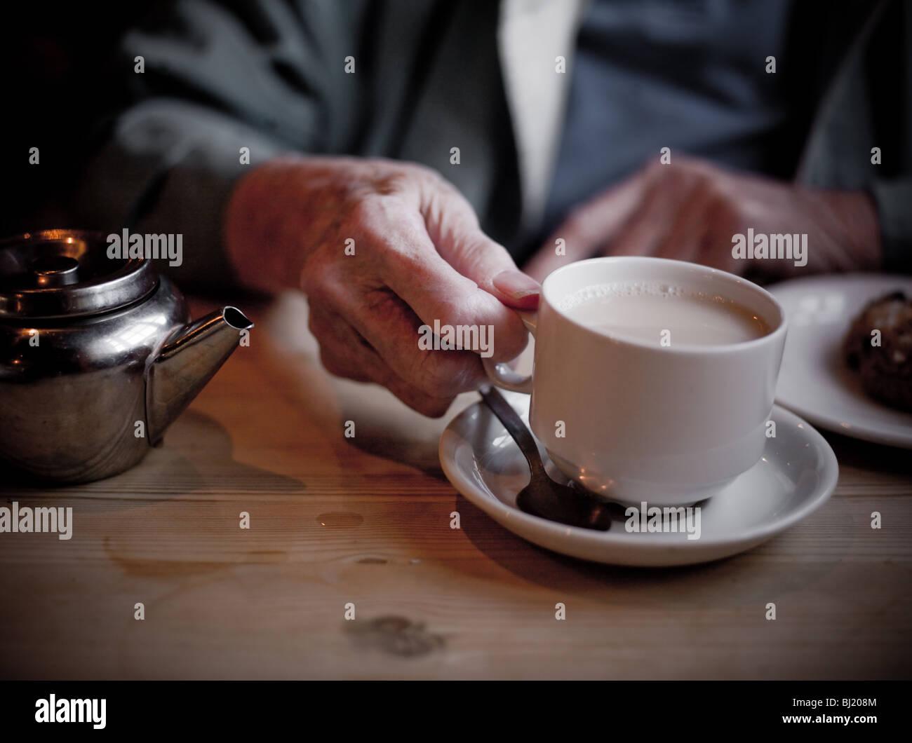 De vieilles dames mains tenant une tasse de thé. Photo Stock