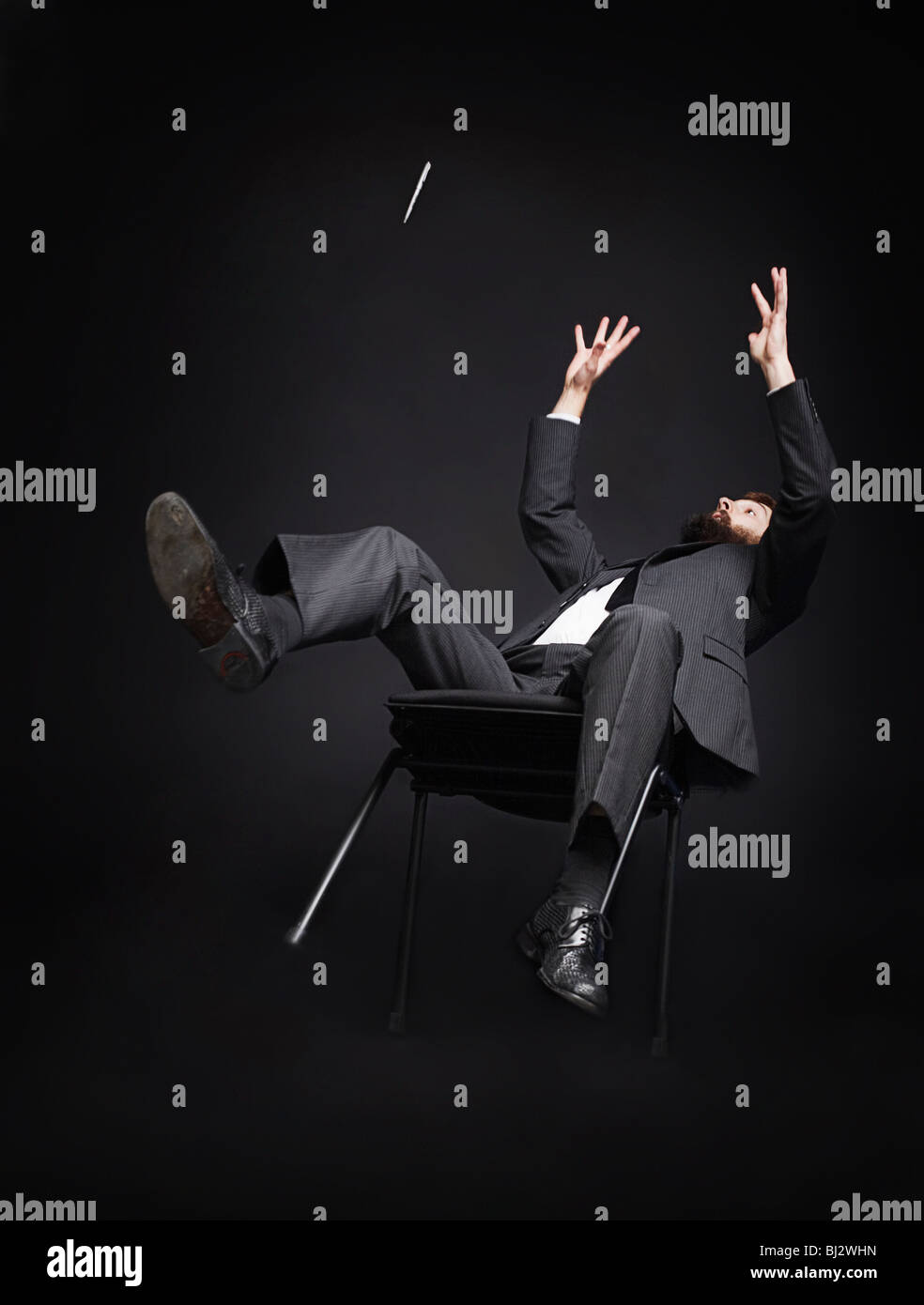 L'homme tomber d'une chaise Photo Stock
