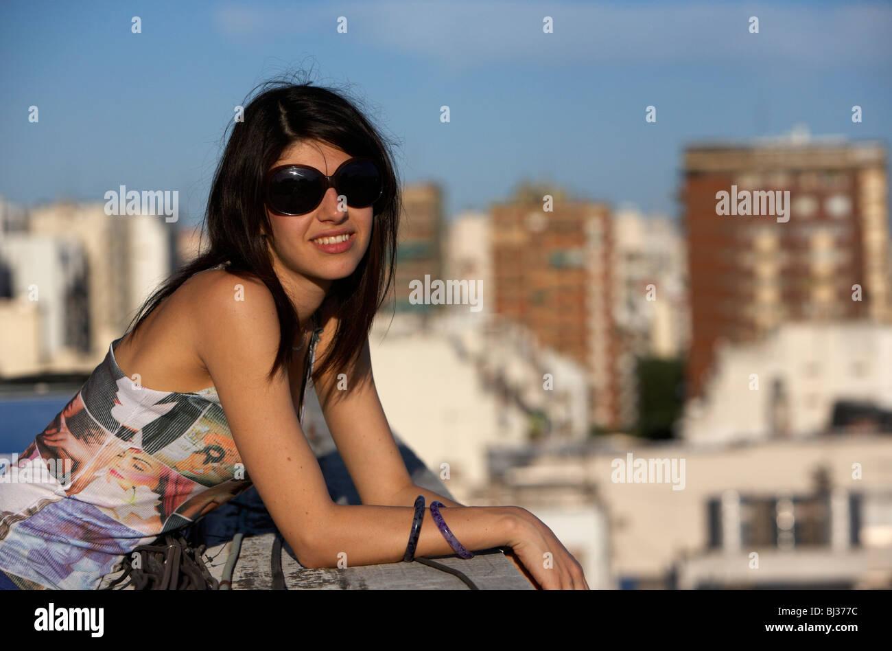 Jeune femme latine hispanique détendu s'appuyant sur une terrasse sur le toit à la recherche à Photo Stock