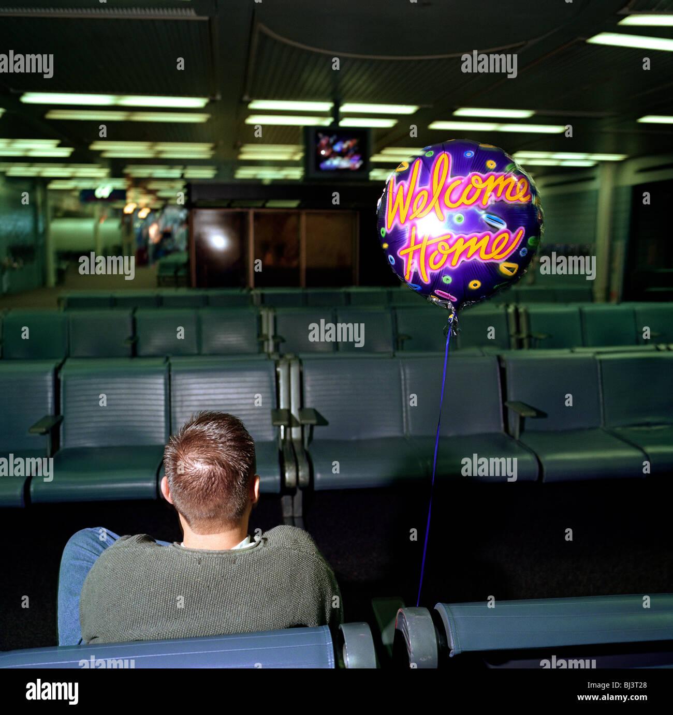 Dans un sombre porte des arrivées à l'aéroport O'Hare de Chicago, un jeune homme est assis patiemment sur son propre Banque D'Images