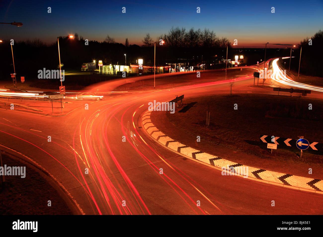 Les voitures et les feux de signalisation des sentiers sur un rond-point Photo Stock