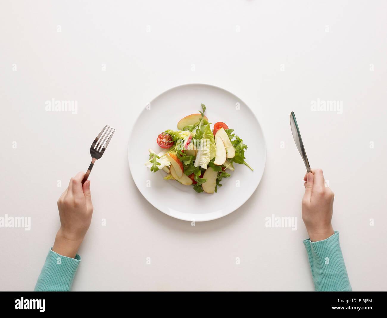 Mains par une assiette de salade Photo Stock