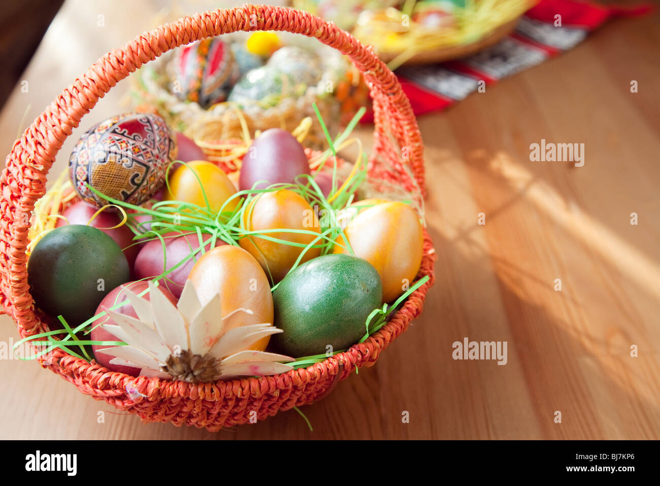 Les oeufs peints de Pâques dans un panier sur la table Photo Stock