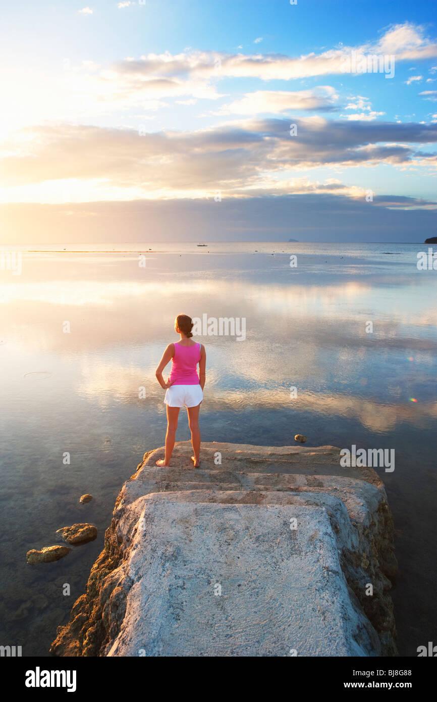 Girl à la fin de la jetée à la recherche dans le coucher du soleil; le sud de Batangas, Matabungkay Photo Stock