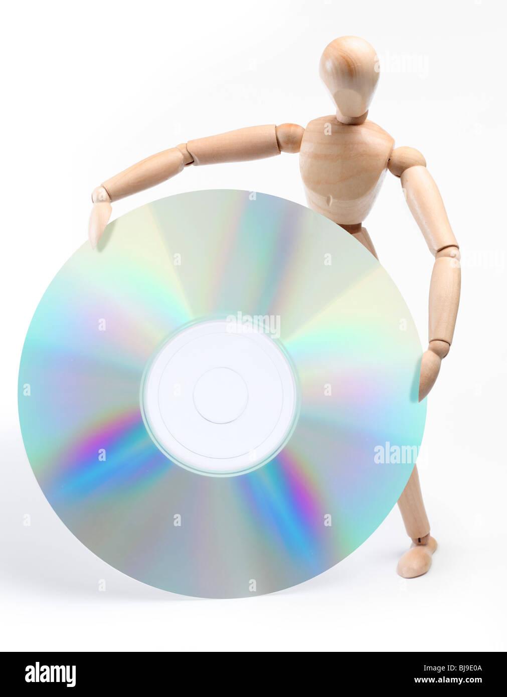Homme de bois tenant un grand disque d'ordinateur. Isolated over white Photo Stock