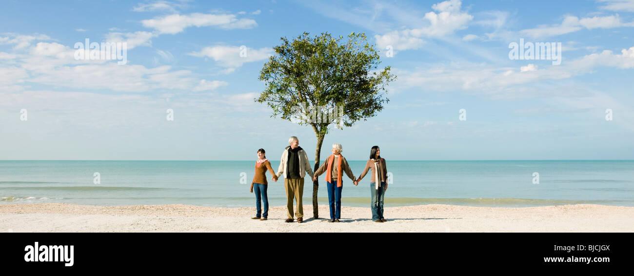 Ecology concept, groupe de gens debout en face d'arbre, holding hands Photo Stock