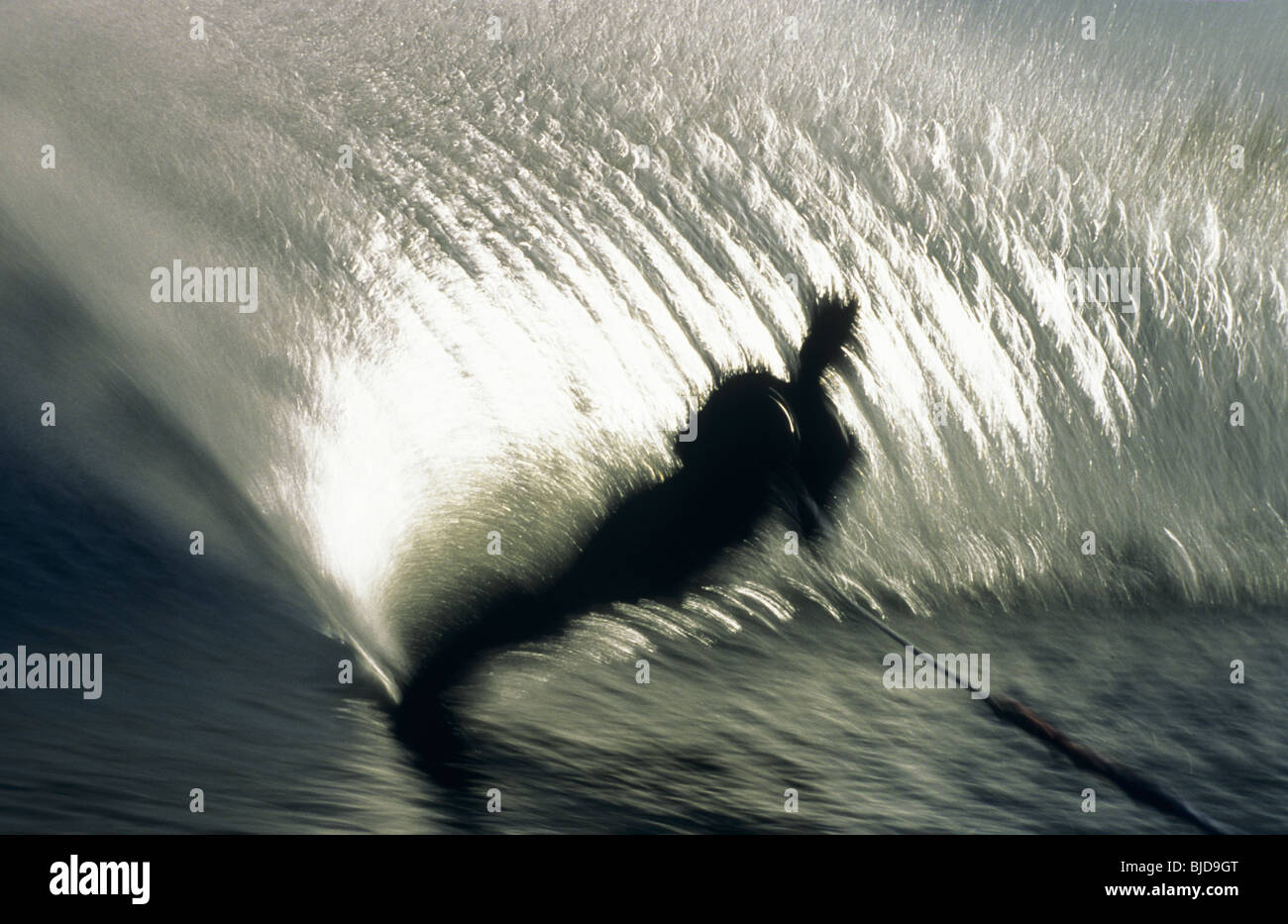Skieur dans l'eau action crée plume d'eau comme il coupe retour Photo Stock