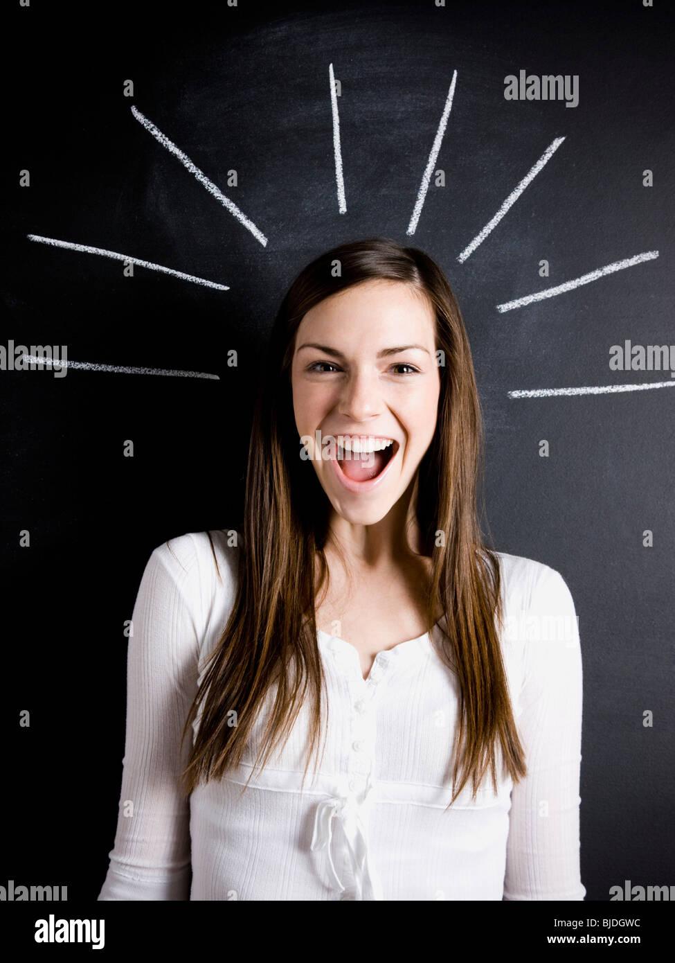 Jeune femme contre une ardoise Photo Stock