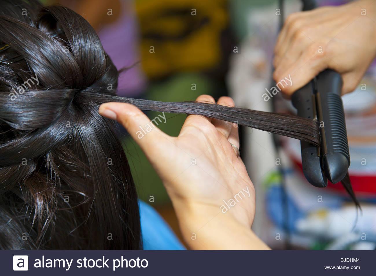 Tirant les cheveux avec un fer à repasser tout droit Photo Stock
