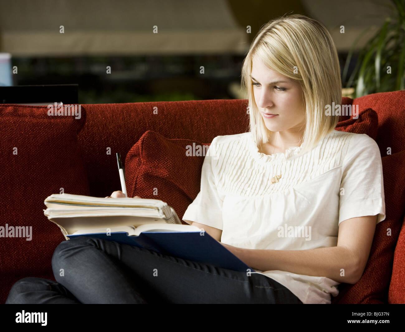 Femme lisant sur le canapé Photo Stock