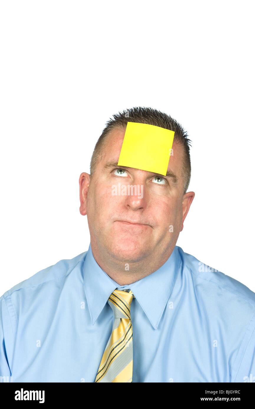 Un homme d'affaires avec un post-it sur son front. Photo Stock