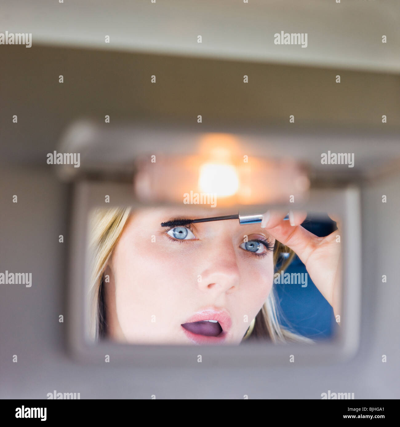 Femme maquiller dans le miroir de pare-soleil de la voiture Photo Stock