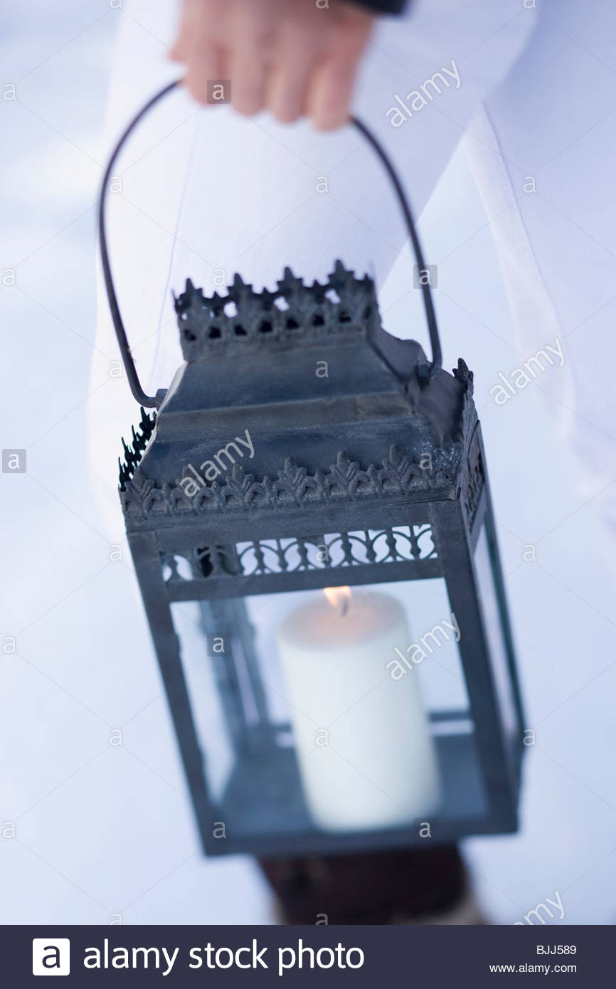 Personne transportant Christmassy lantern hors des portes Photo Stock