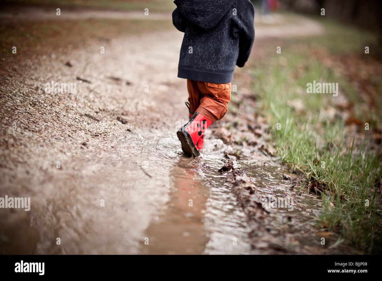 Jeune garçon portant des bottes de pluie promenades à travers une flaque d'eau. Photo Stock