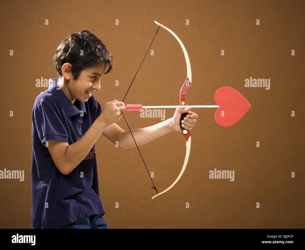 Garçon avec arc et flèche avec coeur sur elle Banque D'Images
