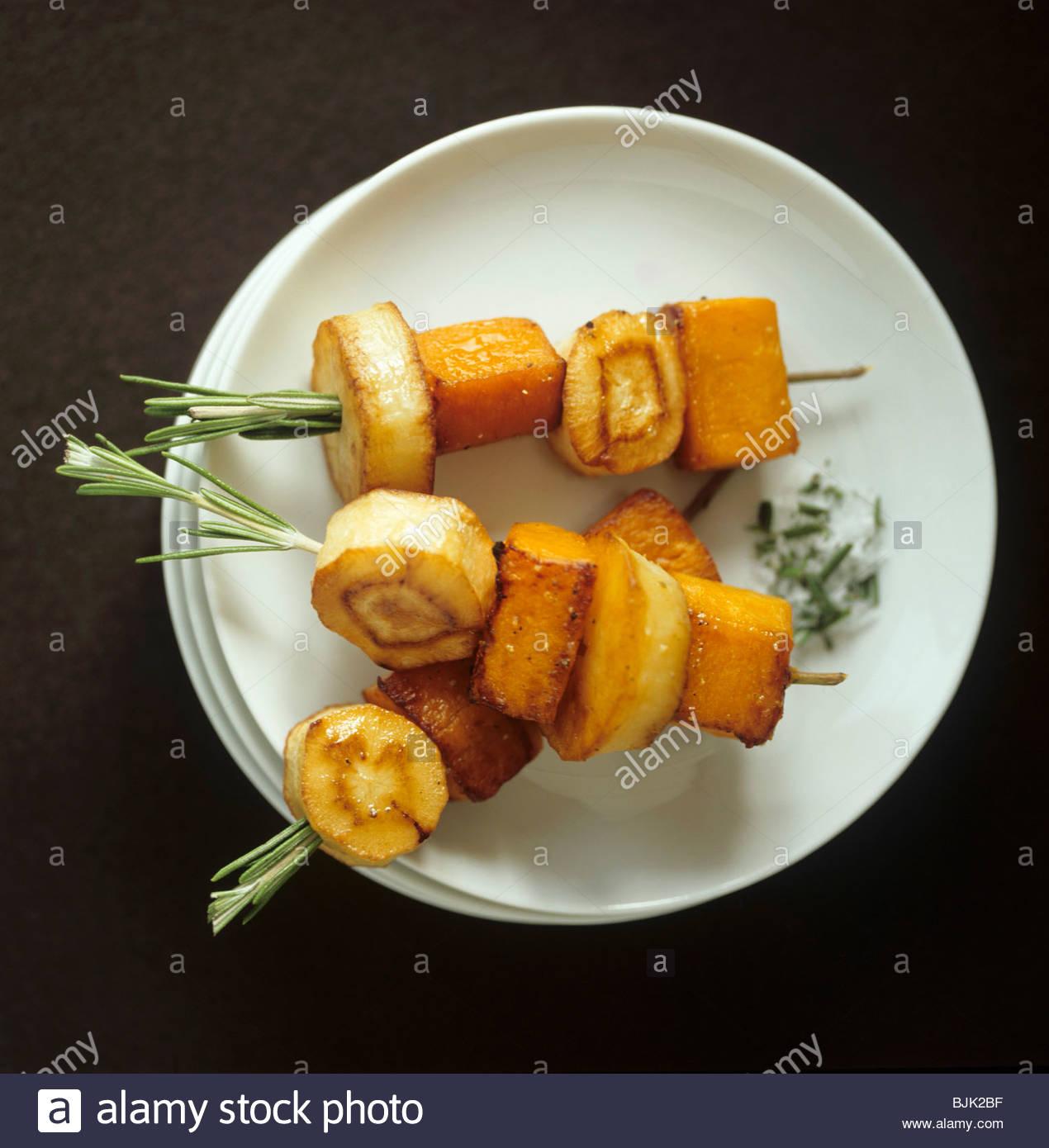 La patate douce cuite au four et le panais sur des brochettes de romarin Photo Stock
