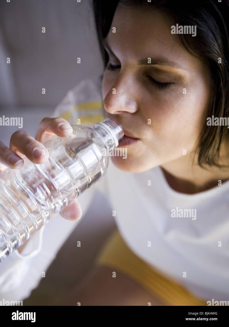 Femme assise et de boire de l'eau en bouteille Photo Stock
