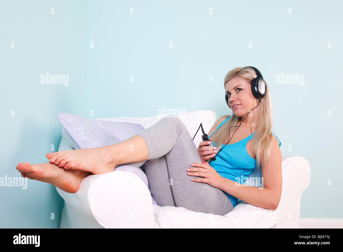 Blonde femme était assise dans un fauteuil avec un casque sur l'écoute de la musique. Photo Stock