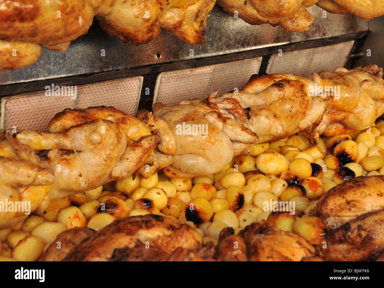 Un poulet entier à grande échelle commerciale et de pommes de terre rôti rôtisserie. Photo Stock
