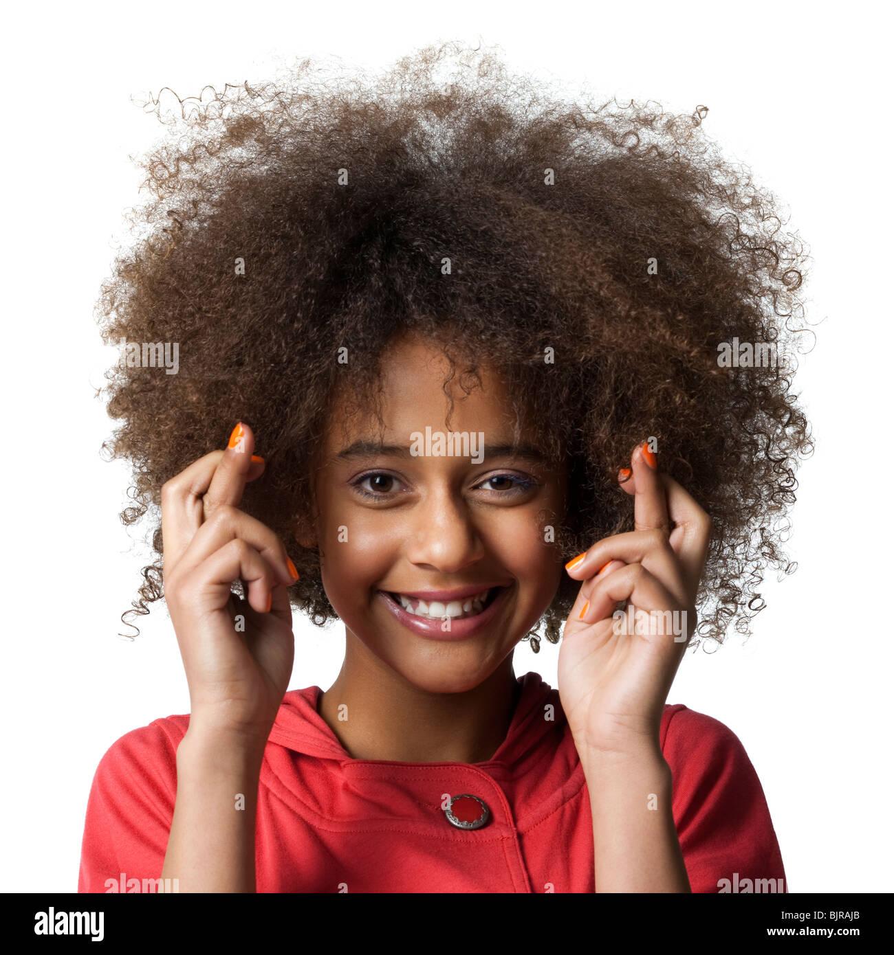 Studio portrait of teenage girl (12-13) avec les doigts croisés Photo Stock