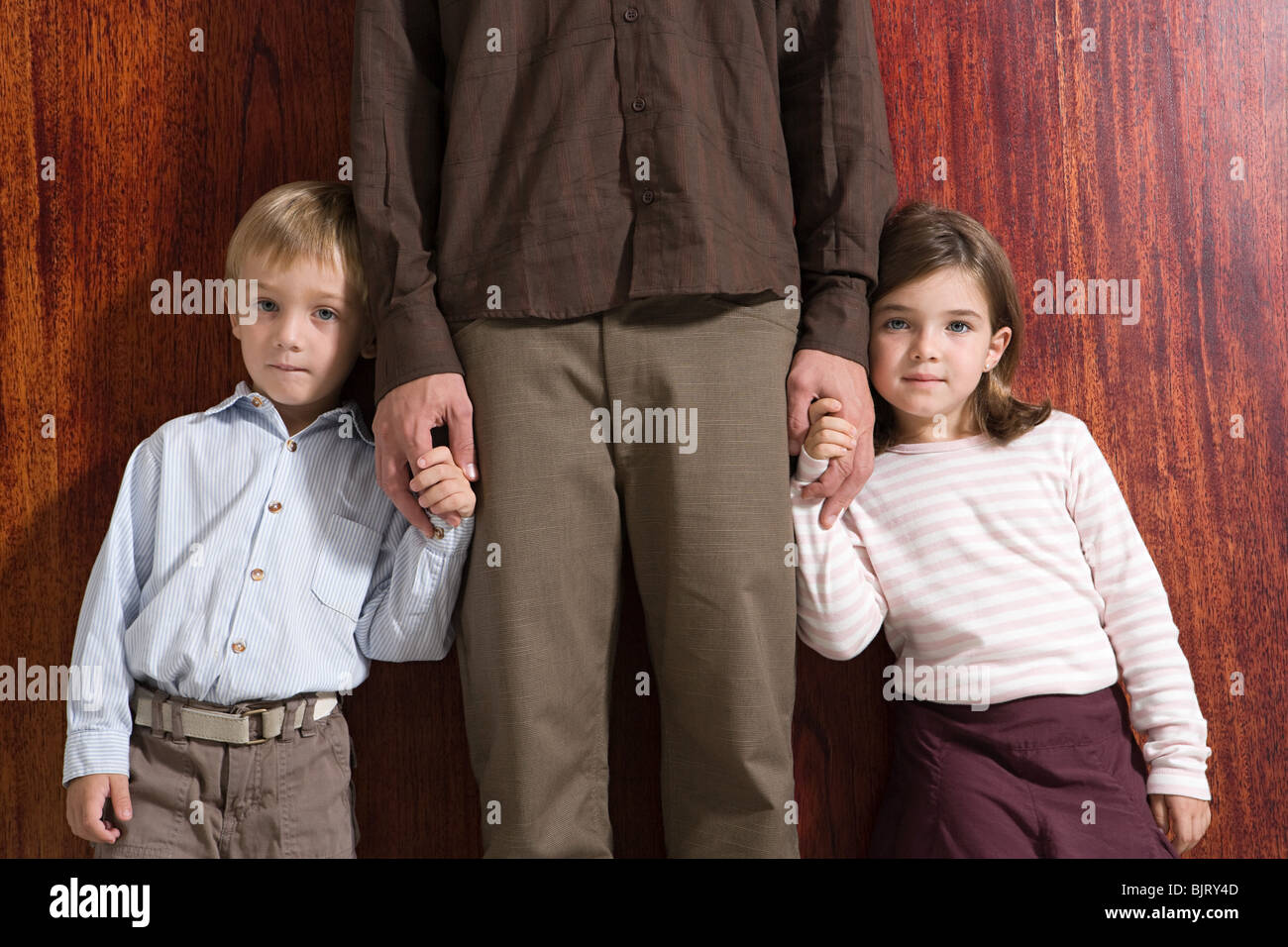 Les enfants tenant la main de leur père Banque D'Images