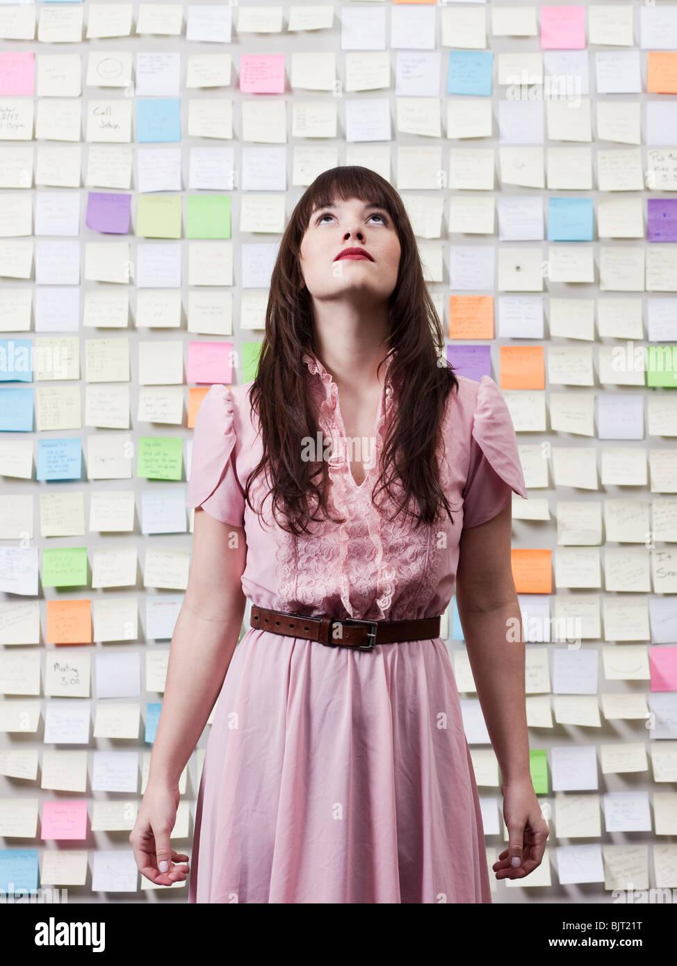 Portrait de femme dans la salle avec des murs couverts de notes adhésives Photo Stock