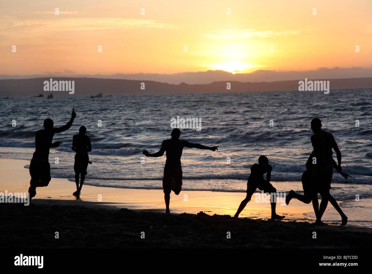 Amis jouant au football sur la plage au coucher du soleil. Plage de la ville de Benguela, en Angola. Afrique © Zute Banque D'Images