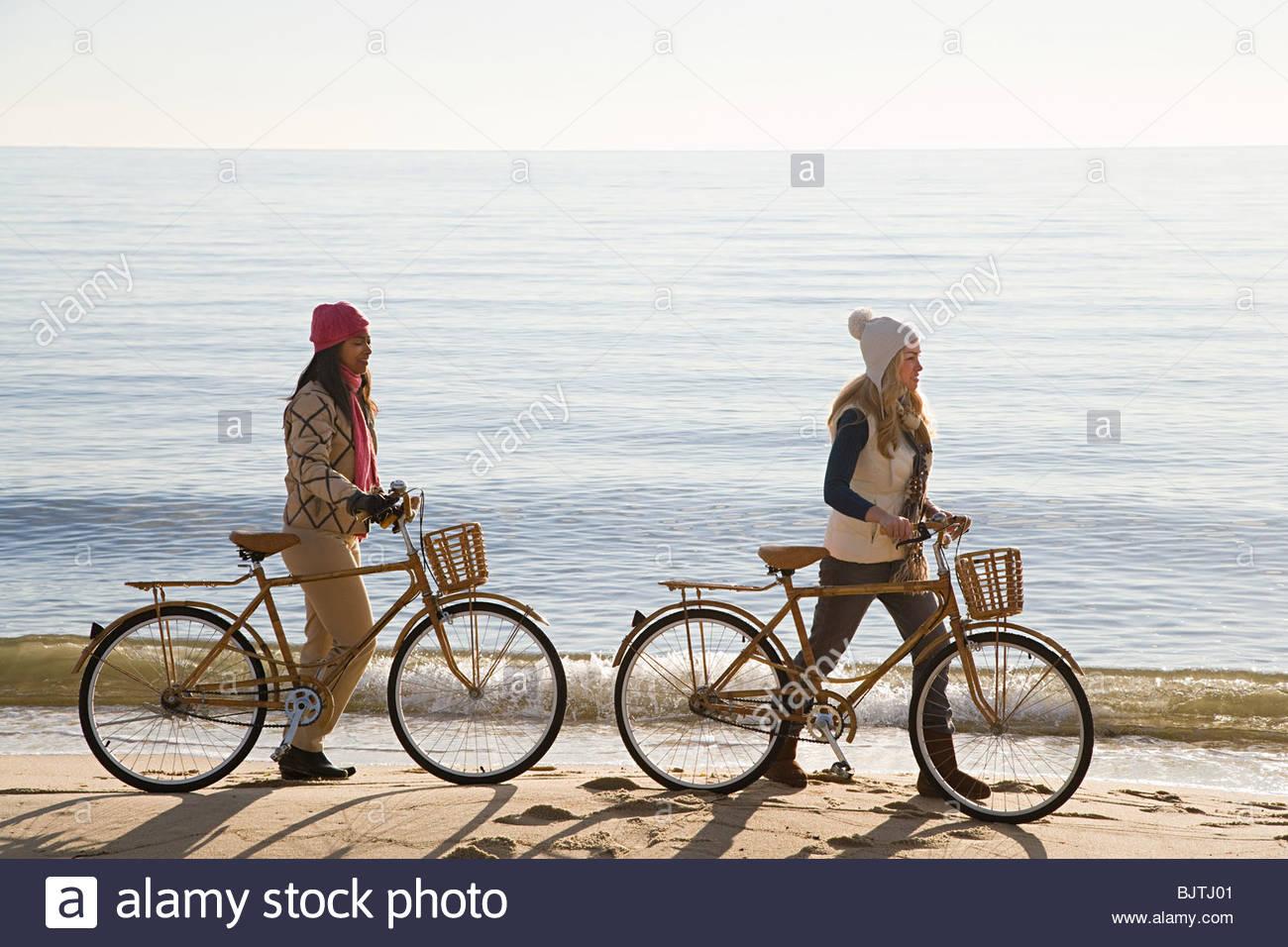 Les femmes par la mer avec des bicyclettes Photo Stock