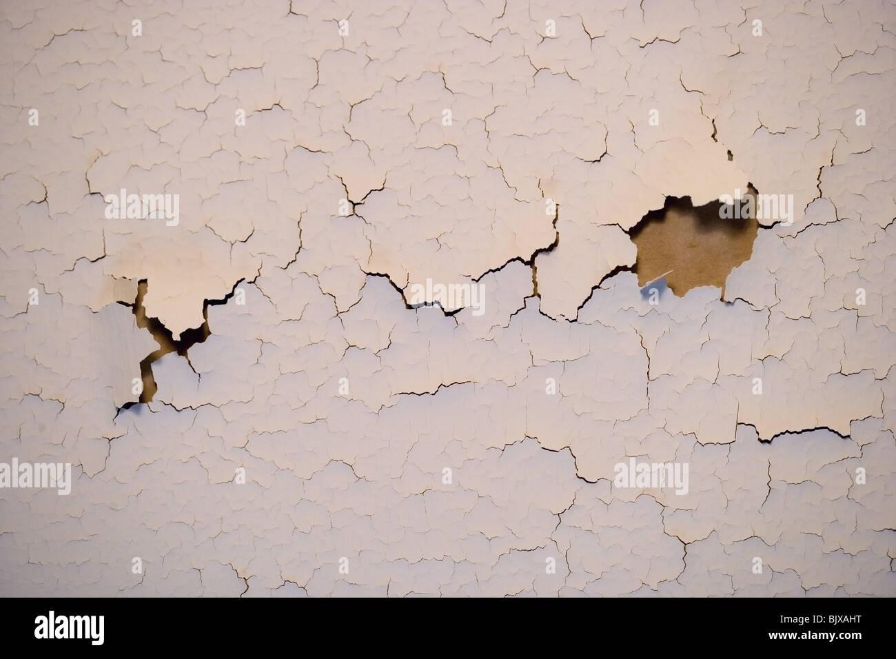 Fissures de la peinture sur un mur intérieur d'une maison. Photo Stock