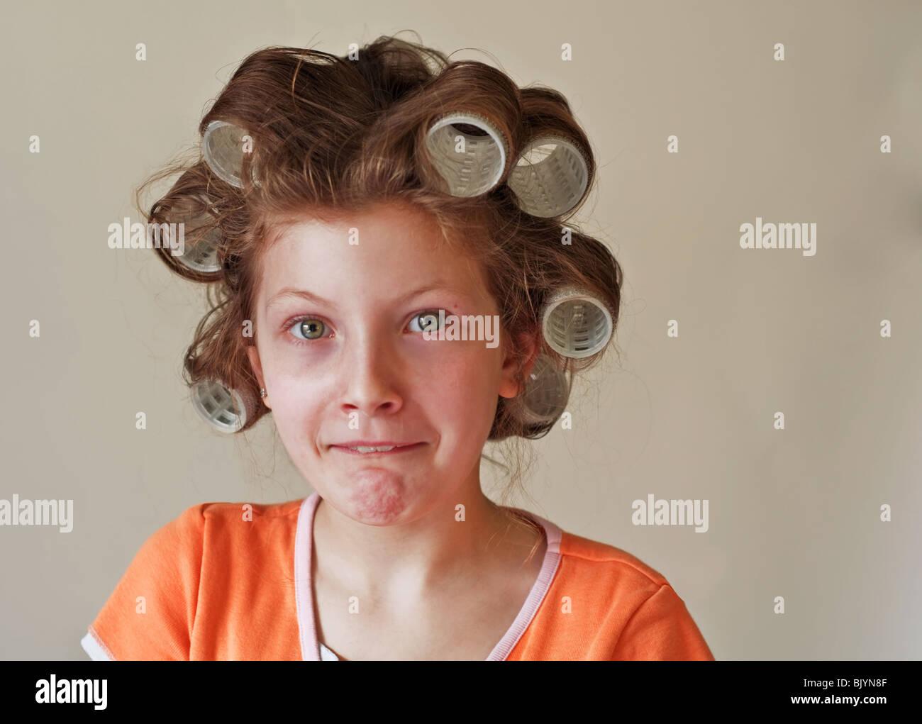 Cette image est une 9 ans fille aux yeux verts, a ses cheveux en rouleaux (curling) et d'avoir un soin du visage. Photo Stock