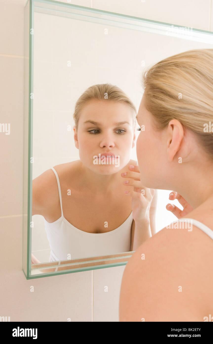 La beauté féminine dans la peau de l'inspection mirror Photo Stock