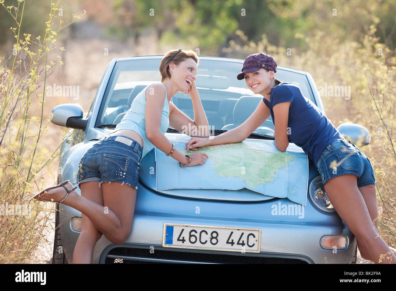 Deux femmes la lecture d'une carte sur un capot de voiture Photo Stock