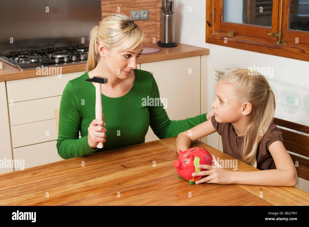 Mère et fille se fissurer une tirelire Photo Stock