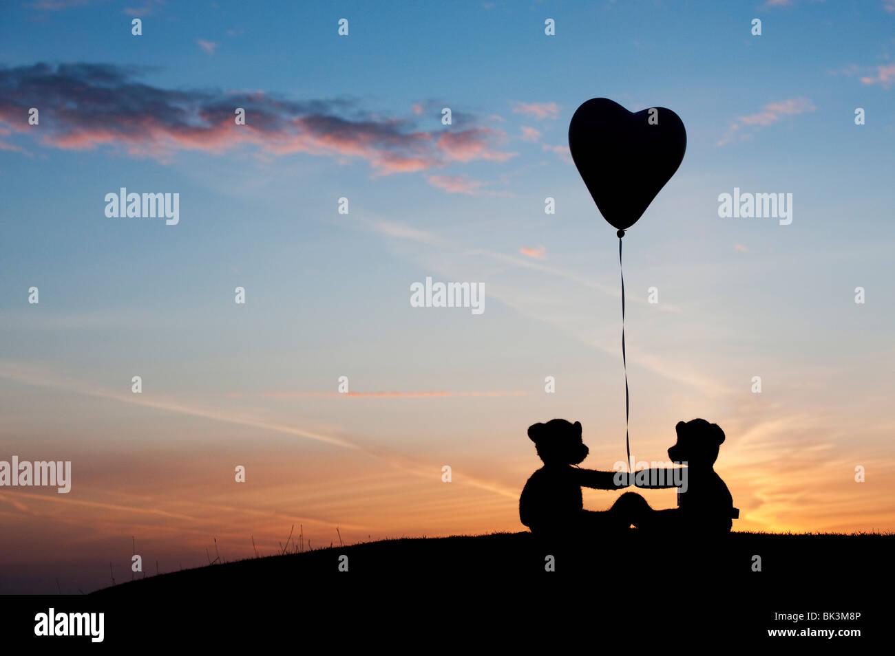 Deux nounours tenant un ballon d'hélium en forme de coeur au lever du soleil. Still Life silhouette Photo Stock