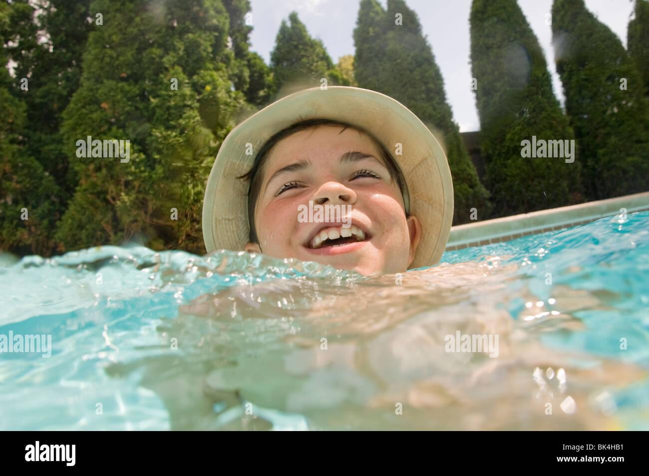 Boy wearing hat in swimming pool Photo Stock