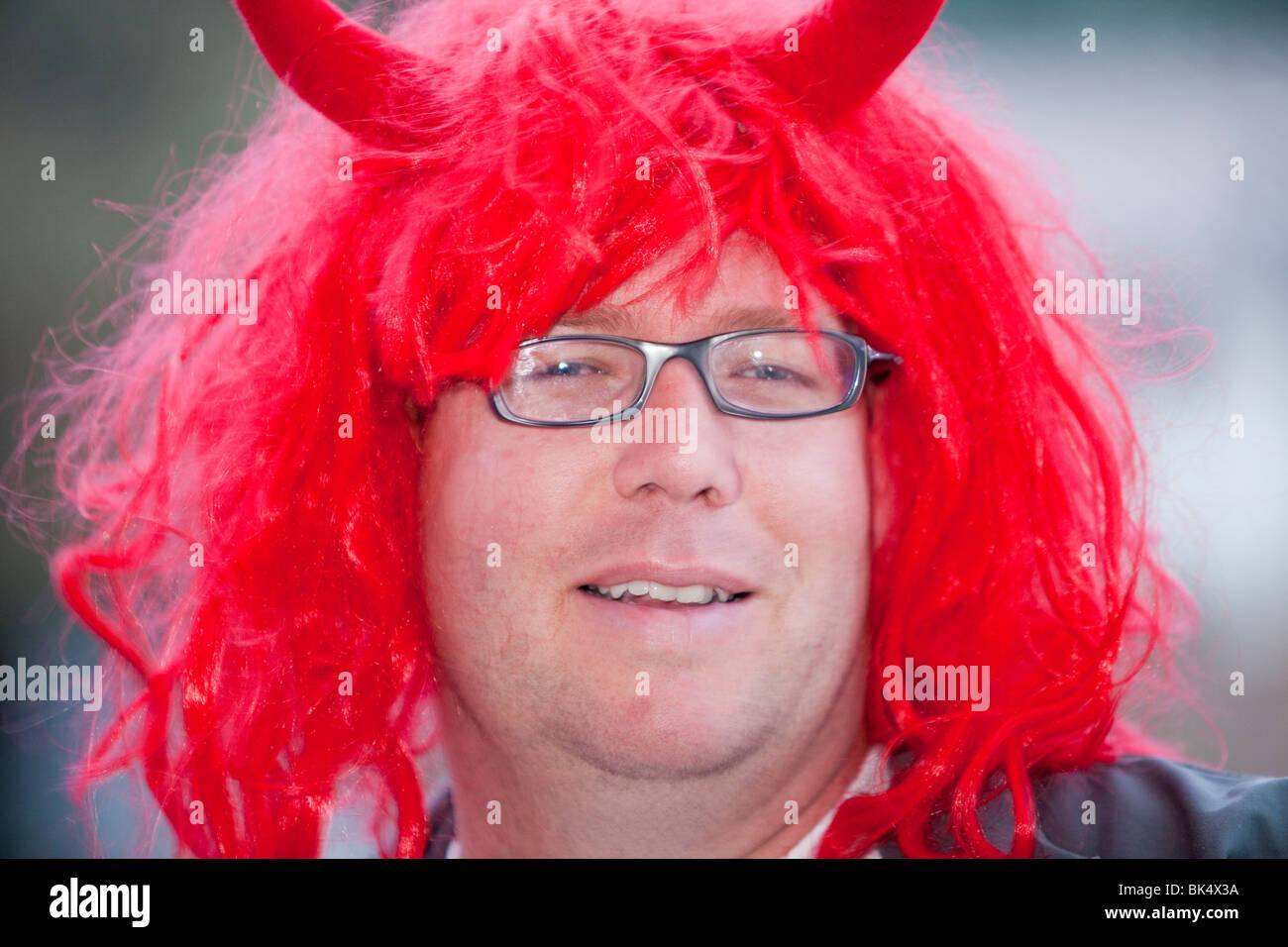 Un homme portant une perruque rouge et devil