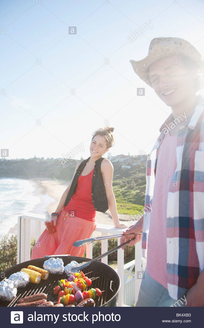 L'homme et la femme ayant tendance barbecue avec ocean in background Photo Stock
