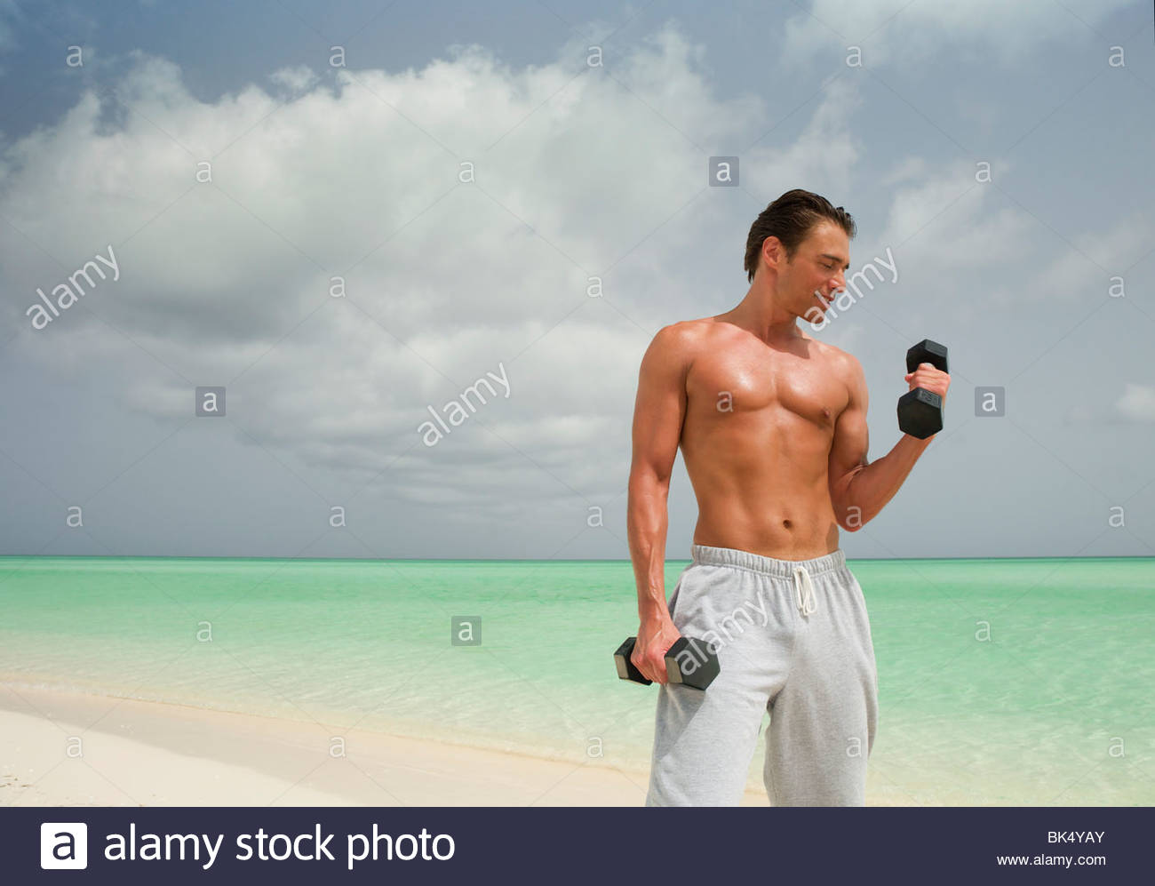 Man on beach faisant de biceps avec haltères Photo Stock