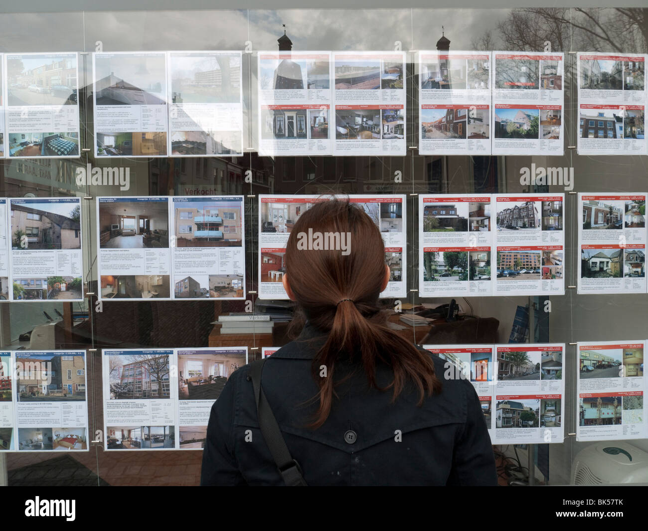 Femme à la recherche de maisons à vendre à des agents immobiliers fenêtre dans Utrecht Pays Photo Stock