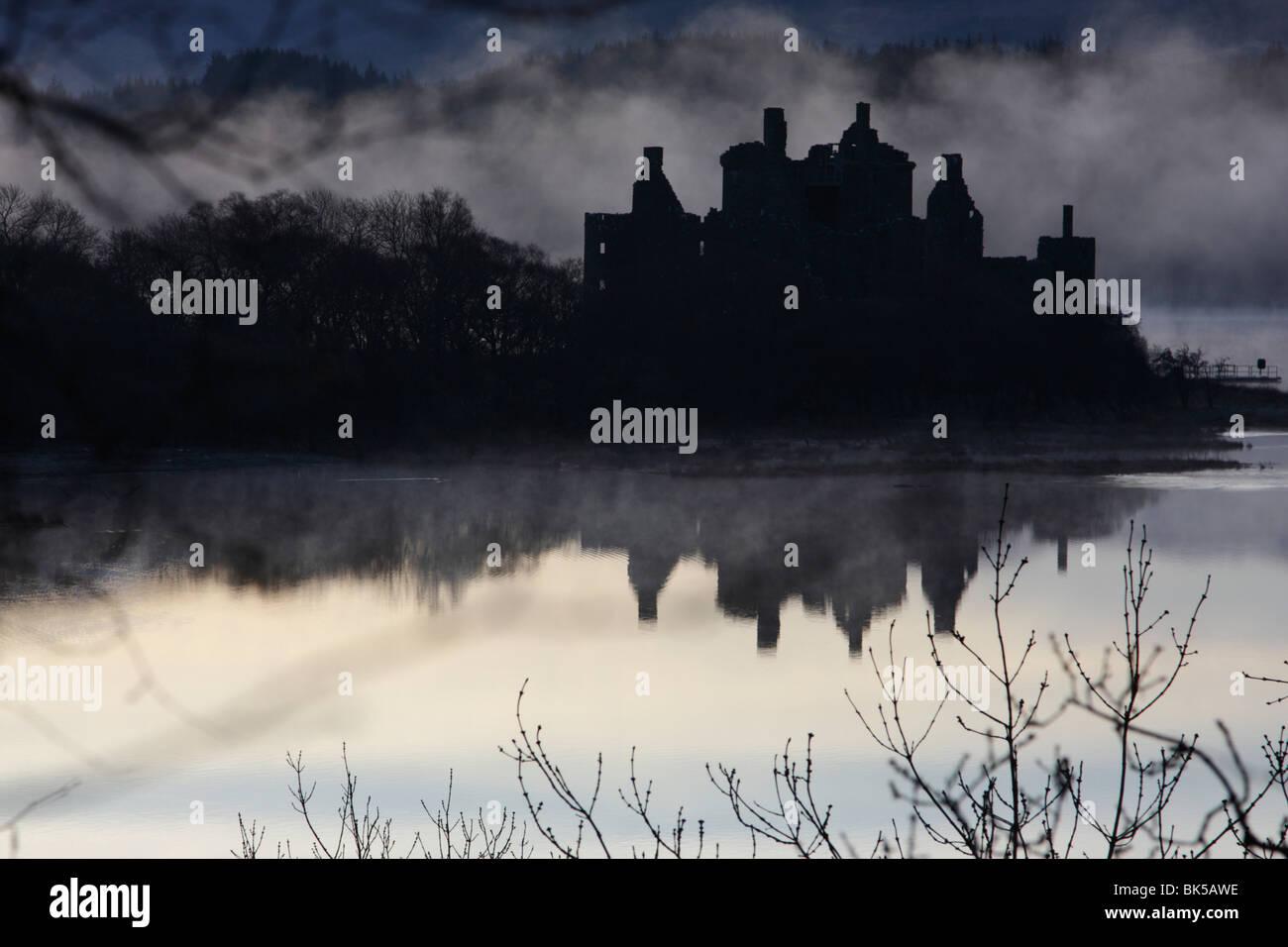 Kilchurn Castle sur les rives du Loch Awe, Ecosse, enveloppée de brouillard tôt le matin Banque D'Images