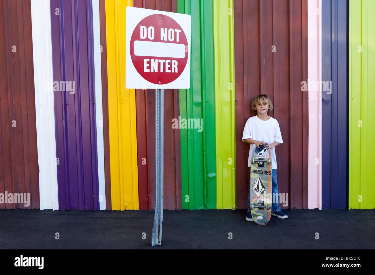 Garçon avec skateboard en face de mur à rayures colorées Photo Stock