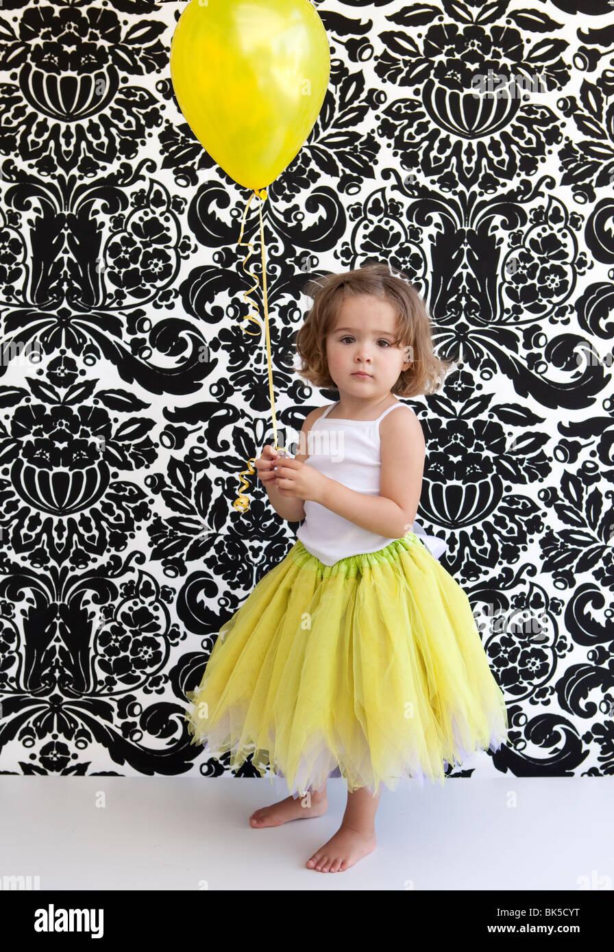 Petite fille aux ballons et tutu jaune Photo Stock