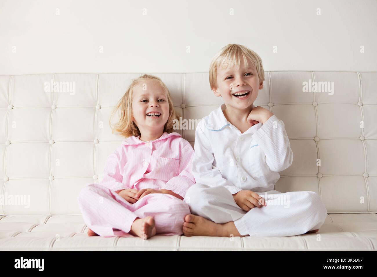 Les jeunes enfants en pyjama, assis sur le canapé Photo Stock