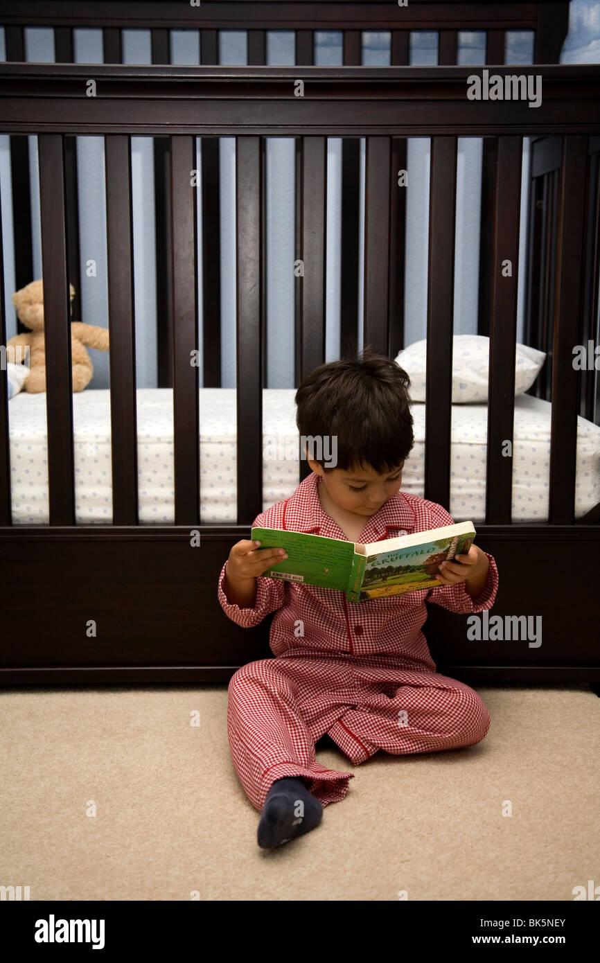 Trois ans la lecture d'un livre avant le coucher Banque D'Images