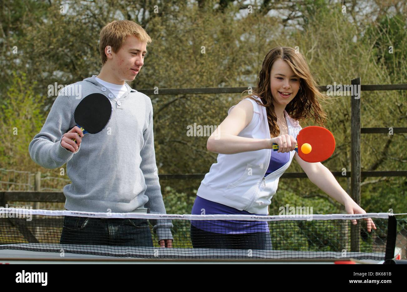 Adolescents jouant une partie de tennis de table dans leur jardin Photo Stock