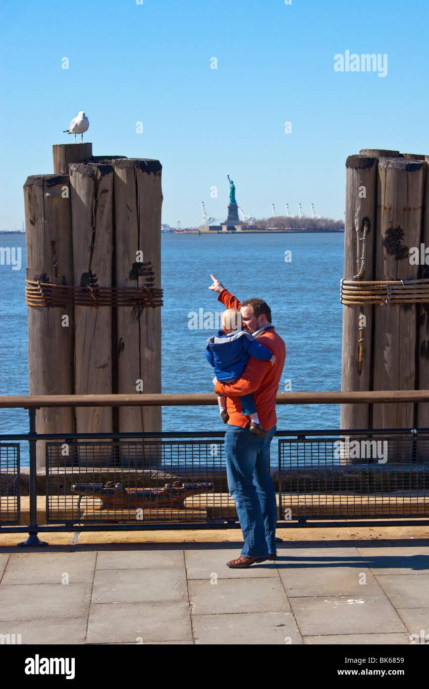 Père et fils en face de la Statue de la Liberté à New York, Manhattan Photo Stock