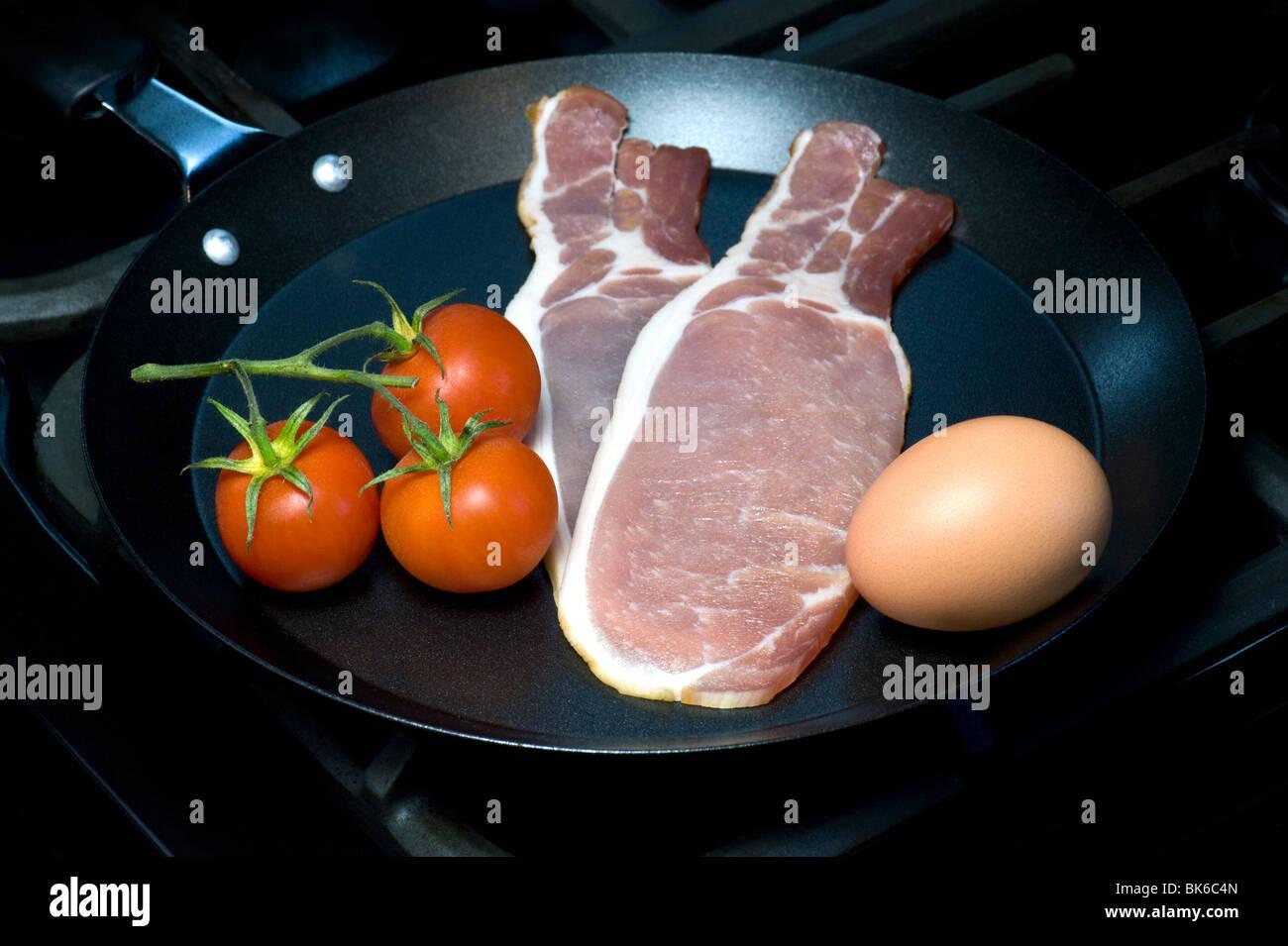 Oeufs, bacon et tomates, les ingrédients pour un petit-déjeuner anglais traditionnel Photo Stock