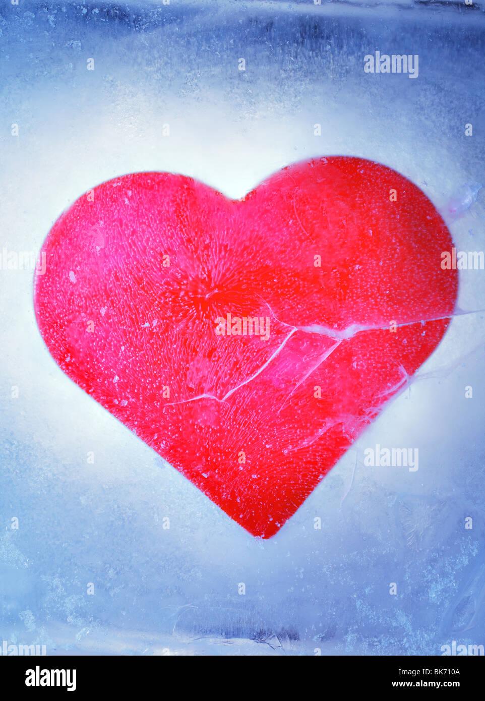 Un cœur rouge congelé dans un bloc de glace Photo Stock