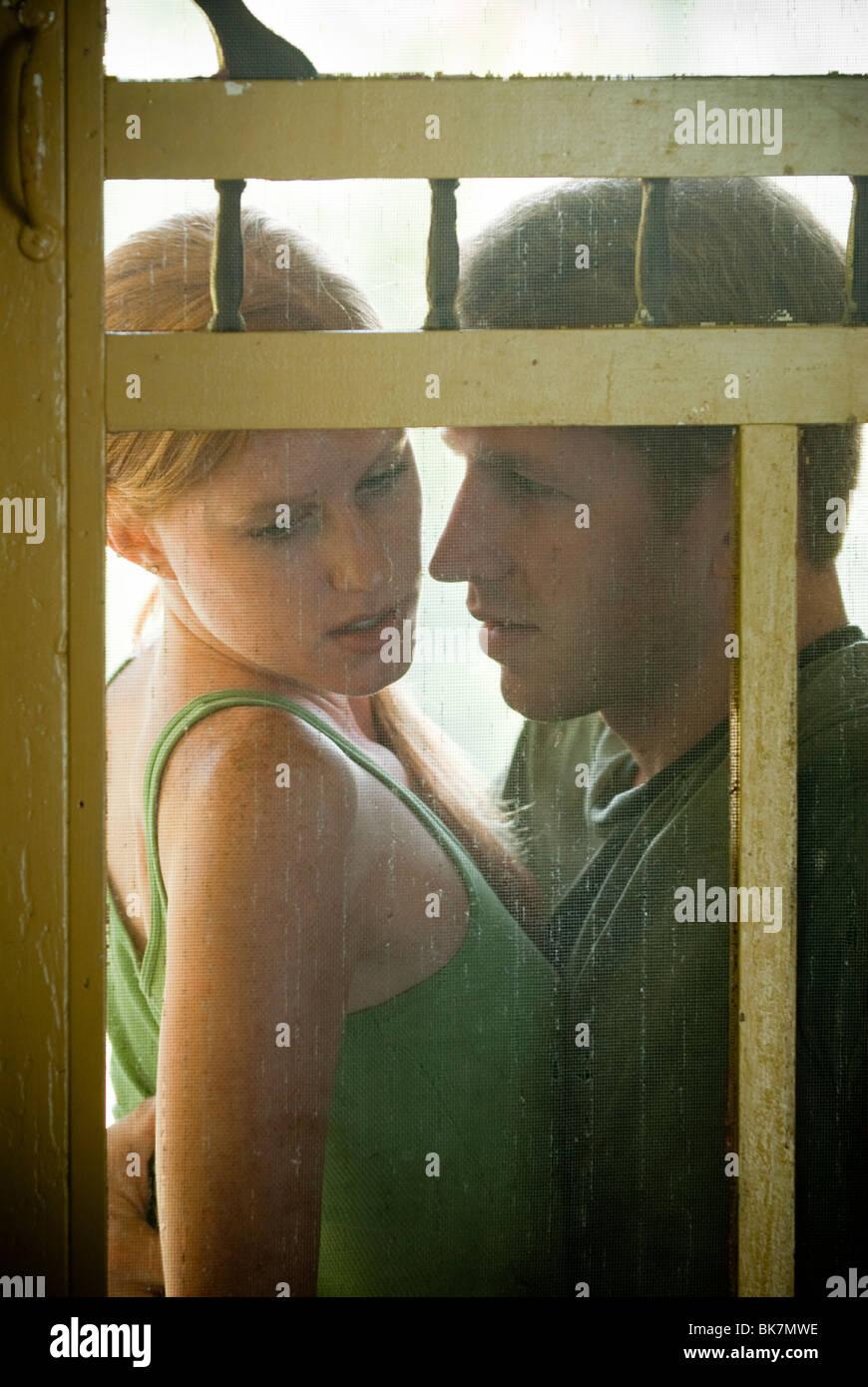 Jeune couple assis sur le porche vu à travers la porte du tamis Photo Stock